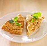 Dos pedazos de empanada de manzana con la menta adornan. Foto de archivo