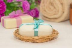 Dos pedazos de jabón con una cesta con arcos, flores, toalla a Imagen de archivo
