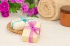 Dos pedazos de jabón con una cesta con arcos, flores, toalla a Foto de archivo libre de regalías