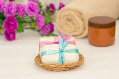 Dos pedazos de jabón con una cesta con arcos, flores, toalla a Foto de archivo