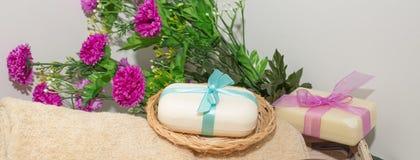 Dos pedazos de jabón con una cesta con arcos, flores y toalla Fotos de archivo