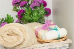 Dos pedazos de jabón con una cesta con arcos, flores y toalla Foto de archivo libre de regalías