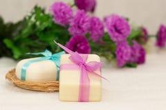 Dos pedazos de jabón con una cesta con un arco y las flores Imagenes de archivo