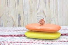 Dos pedazos de jabón rojo y amarillo en la tabla de madera Fondo rústico Accesorios del balneario del baño Tapetito de la tabla c Imágenes de archivo libres de regalías