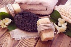 Dos pedazos de jabón seco con un jazmín, la toalla, la piedra pómez y una estopa Foto de archivo libre de regalías