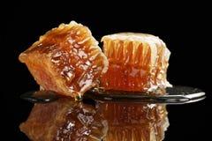Dos pedazos de panal orgánico con la miel aislada en fondo negro Imagen de archivo