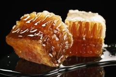 Dos pedazos de panal orgánico con la miel aislada en fondo negro Imagen de archivo libre de regalías