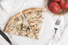 Dos pedazos de pizza en una placa y tomates frescos en un mantel blanco Imagenes de archivo