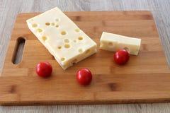 Dos pedazos de queso del queso con los tomates en una tabla de cortar Imágenes de archivo libres de regalías