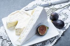 Dos pedazos de quesos blandos franceses brie y camembert con el molde blanco y el olor fuerte, sirvieron con los higos maduros fr fotos de archivo