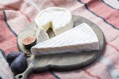 Dos pedazos de quesos blandos franceses brie y camembert con el molde blanco y el olor fuerte, sirvieron con los higos maduros fr imagenes de archivo