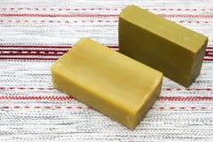 Dos pedazos del jabón orgánico hecho a mano natural del aceite de oliva en la tabla de madera Fondo rústico Accesorios del balnea Imagen de archivo libre de regalías