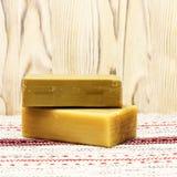 Dos pedazos del jabón orgánico hecho a mano natural del aceite de oliva en la tabla de madera Fondo rústico Accesorios del balnea Fotos de archivo libres de regalías