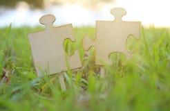 Dos pedazos del rompecabezas puestos en la hierba durante tiempo de la puesta del sol con la lente señalan por medio de luces ide Imagenes de archivo