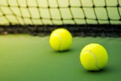 Dos pelotas de tenis en corte verde Fotos de archivo libres de regalías