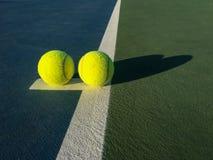 Dos pelotas de tenis en la línea blanca en campo de tenis Foto de archivo