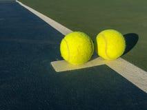 Dos pelotas de tenis en la línea blanca en campo de tenis Imágenes de archivo libres de regalías