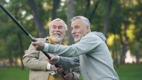 Dos pensionistas que cogen los pescados grandes, tirando del giro junto, ayuda de la amistad metrajes