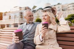 Dos pensionistas se están sentando en un banco con un vidrio de café en sus manos Sientan el abarcamiento Imágenes de archivo libres de regalías