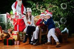 Dos pequeña Santa Clauses que afirma un regalo Imagenes de archivo