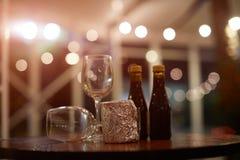 Dos pequeñas botellas de vino en una tabla de madera con dos cubiletes de cristal foto de archivo libre de regalías