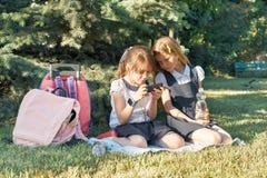 Dos pequeñas colegialas que usan smartphone Niños que juegan, lectura, mirando el teléfono imagenes de archivo