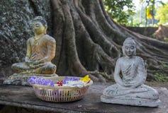 Dos pequeñas estatuas de Buda cerca de la cesta con las flores fotografía de archivo