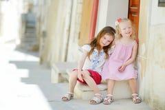 Dos pequeñas hermanas adorables que ríen y que abrazan Imagen de archivo libre de regalías