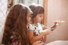Dos pequeñas hermanas agradables vestidas en camisas idénticas cepillan sus dientes en el cuarto de baño fotografía de archivo