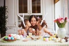Dos pequeñas hermanas con los oídos de conejo blancos en sus cabezas besan a su madre que teñe los huevos para la tabla de Pascua imagenes de archivo
