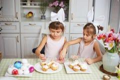 Dos pequeñas hermanas con los oídos de conejo blancos en sus cabezas cocinan las pequeñas tortas de Pascua para la tabla de Pascu imagen de archivo libre de regalías
