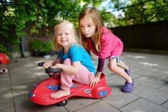 Dos pequeñas hermanas divertidas que conducen un coche del juguete al aire libre Imágenes de archivo libres de regalías