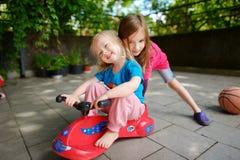 Dos pequeñas hermanas divertidas que conducen un coche del juguete al aire libre Fotos de archivo