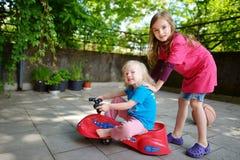 Dos pequeñas hermanas divertidas que conducen un coche del juguete al aire libre Fotografía de archivo