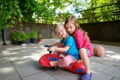 Dos pequeñas hermanas divertidas que conducen un coche del juguete al aire libre Fotografía de archivo libre de regalías