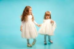 Dos pequeñas hermanas en alineadas finas de un blanco Foto de archivo libre de regalías