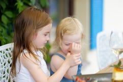 Dos pequeñas hermanas en café del aire libre Imagen de archivo libre de regalías
