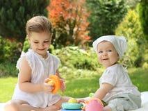 Dos pequeñas hermanas en el jardín del verano Foto de archivo libre de regalías