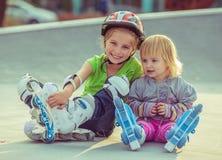 Dos pequeñas hermanas en pcteres de ruedas Foto de archivo libre de regalías