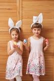 Dos pequeñas hermanas encantadoras en los vestidos con los oídos de conejo blancos en sus cabezas sostienen los huevos teñidos en fotos de archivo libres de regalías