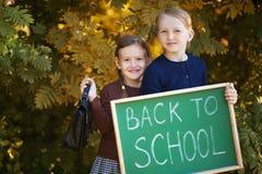 Dos pequeñas hermanas felices de nuevo a escuela Imagen de archivo