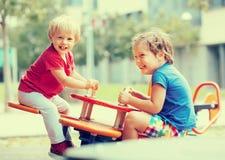 Dos pequeñas hermanas felices en tablero que vacila Imagen de archivo