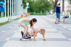 Dos pequeñas hermanas hermosas en pcteres de ruedas Fotos de archivo libres de regalías