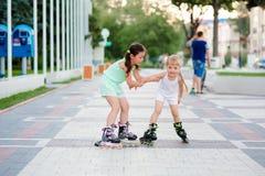 Dos pequeñas hermanas hermosas en pcteres de ruedas Imagenes de archivo
