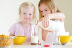 Dos pequeñas hermanas lindas que comen el cereal en una cocina Imagen de archivo