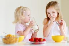 Dos pequeñas hermanas lindas que comen el cereal en una cocina Fotografía de archivo