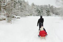 Dos pequeñas hermanas lindas que gozan del trineo montan con su padre en día de invierno nevoso imagenes de archivo