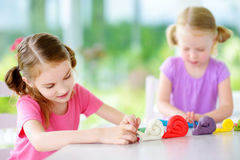 Dos pequeñas hermanas lindas que se divierten así como la arcilla de modelado en una guardería Niños creativos que moldean en cas Foto de archivo