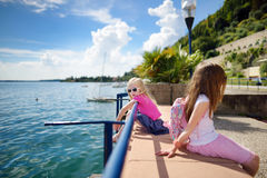 Dos pequeñas hermanas lindas que se divierten en una orilla del lago Garda en Toscolano-Maderno, una pequeña ciudad y comune en l Fotos de archivo libres de regalías