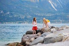 Dos pequeñas hermanas lindas que se divierten en una playa del sul Garda de Limone, de una pequeña ciudad y del comune en la prov Imagen de archivo libre de regalías